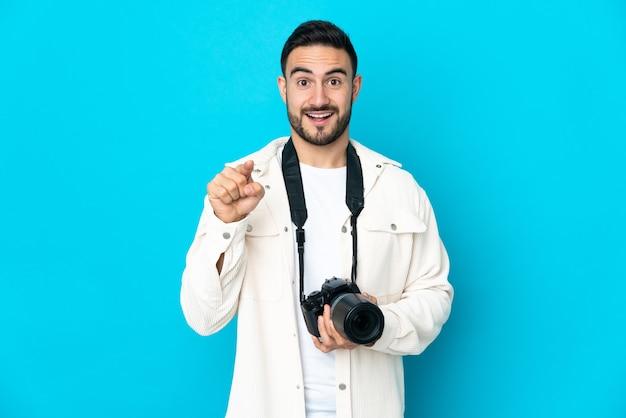 Homme jeune photographe isolé sur mur bleu surpris et pointant vers l'avant