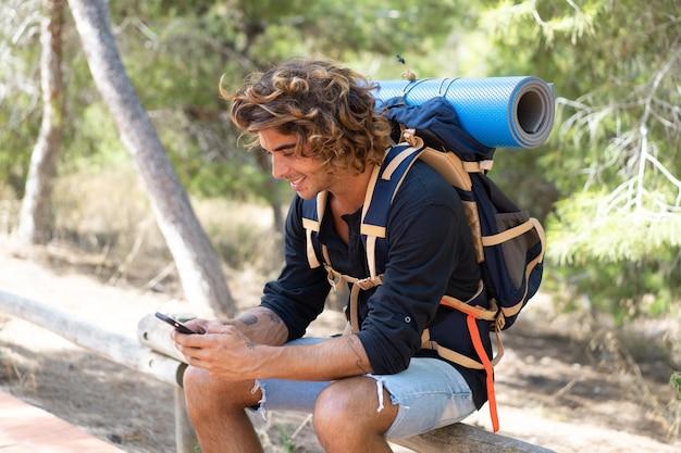 Homme jeune randonneur caucasien passer leurs vacances en camping et appeler ses amis