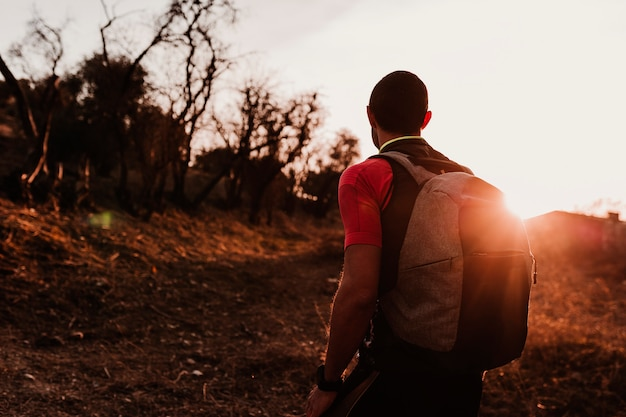 Homme jeune randonneur à la montagne au coucher du soleil. concept sportif
