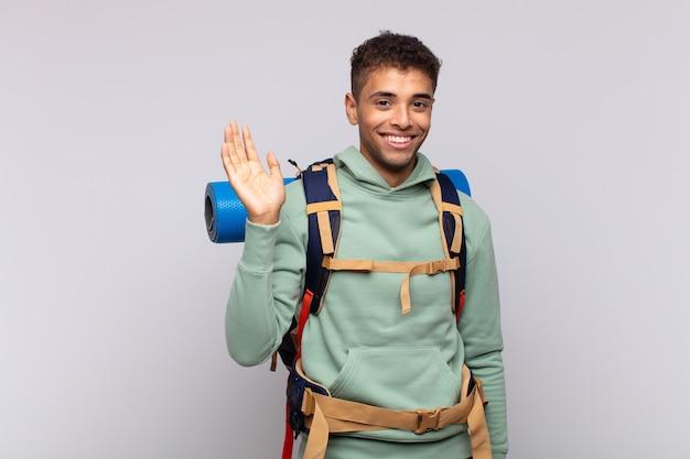 Homme jeune randonneur souriant joyeusement et gaiement, agitant la main, vous accueillant et vous saluant, ou vous disant au revoir