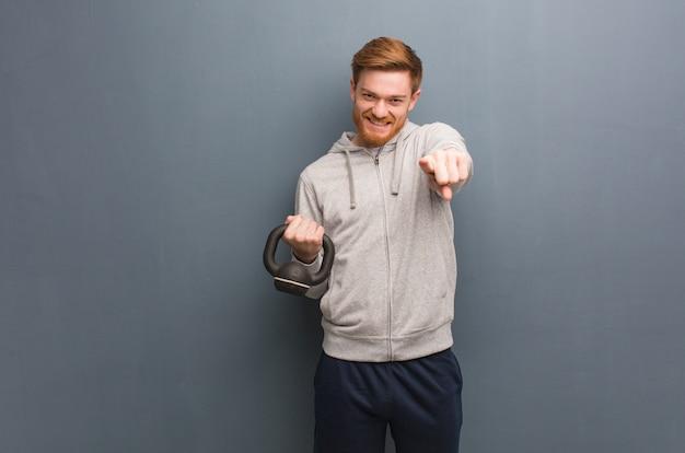 Homme jeune de remise en forme rousse gai et souriant pointant vers l'avant. tenant un haltère.