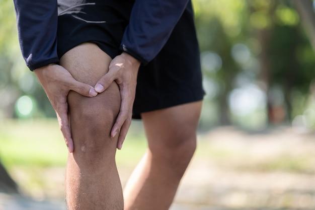 Homme jeune de remise en forme tenant sa blessure à la jambe sportive, muscle douloureux pendant l'entraînement