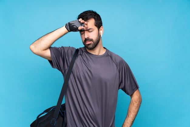 Homme jeune sport avec barbe sur bleu isolé avec expression fatiguée et malade