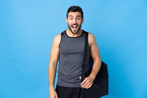 Homme jeune sport avec sac de sport isolé sur mur bleu avec expression faciale surprise