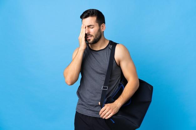 Homme jeune sport avec sac de sport isolé sur mur bleu avec maux de tête