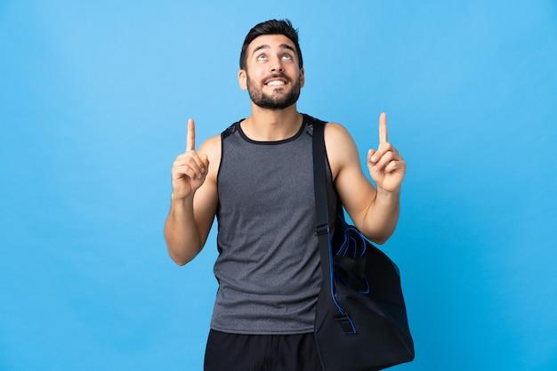Homme jeune sport avec sac de sport isolé sur mur bleu pointant vers le haut une bonne idée