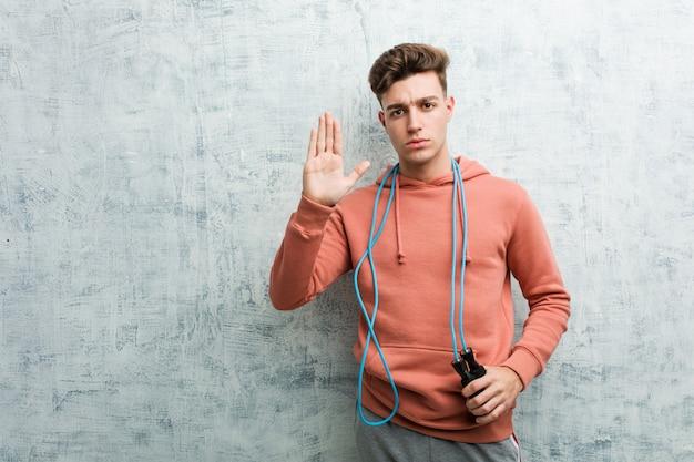 Homme jeune sport tenant une corde à sauter debout avec la main tendue montrant le panneau d'arrêt, vous empêchant.