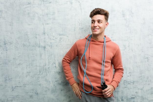 Homme jeune sport tenant une corde à sauter souriant confiant avec les bras croisés.