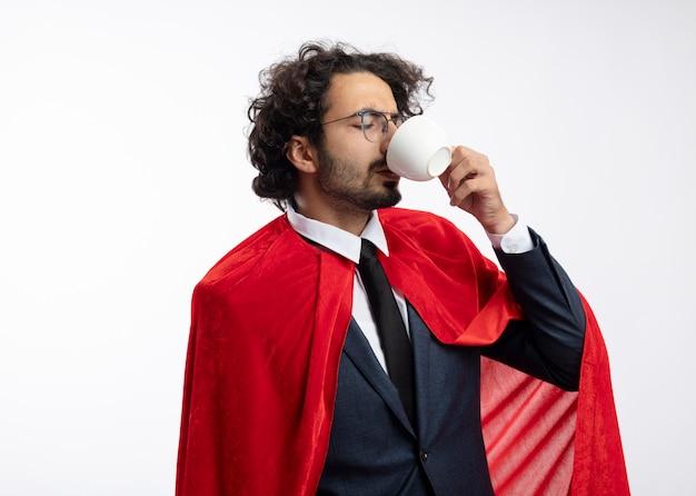 Homme jeune super-héros insatisfait dans des lunettes optiques portant costume avec cape rouge boissons de tasse isolé sur mur blanc