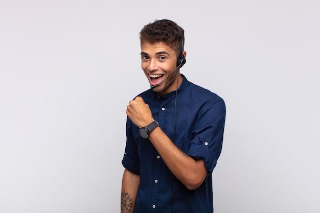 Homme jeune télévendeur se sentant heureux, positif et prospère, motivé face à un défi ou célébrant de bons résultats
