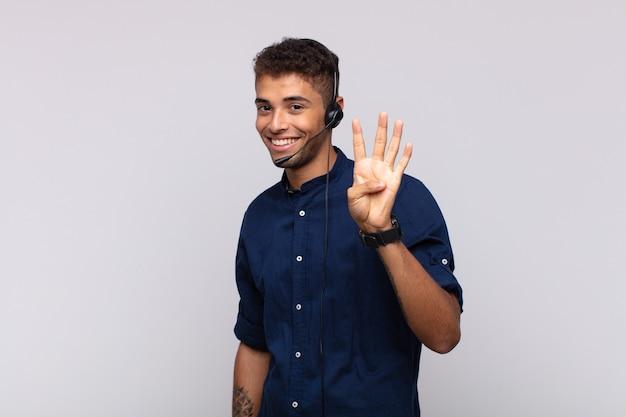 Homme jeune télévendeur souriant et à la sympathique, montrant le numéro quatre ou quatrième avec la main en avant, compte à rebours