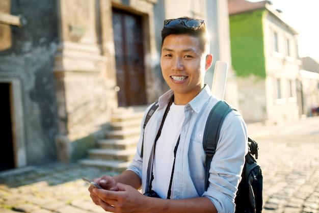 Homme jeune touriste avec mobile à la main en regardant la caméra.