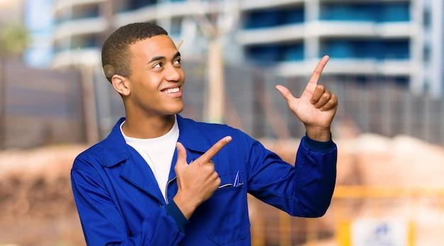 Homme jeune travailleur américain afro pointant avec l'index et levant les yeux sur un chantier de construction