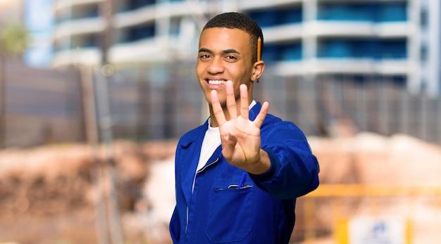 Homme jeune travailleur américain heureux et comptant quatre avec les doigts dans un chantier de construction