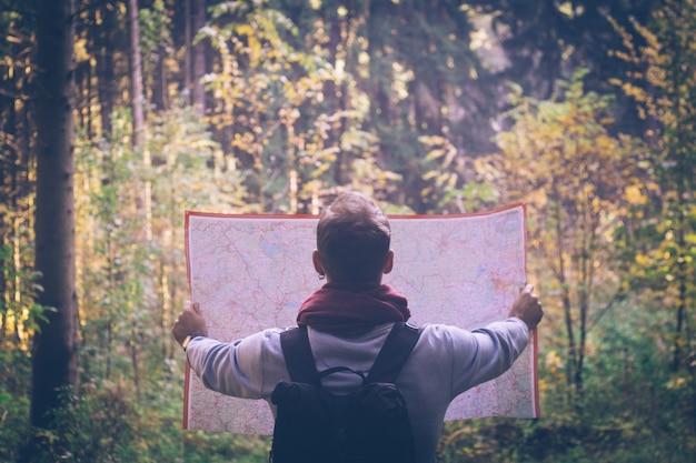 Homme jeune voyageur avec carte, sac à dos à la forêt verte automne en journée ensoleillée.