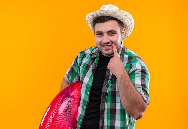 Homme jeune voyageur en chemise à carreaux et chapeau d'été tenant l'anneau gonflable pointant avec le doigt sur son sourire debout sur le mur orange