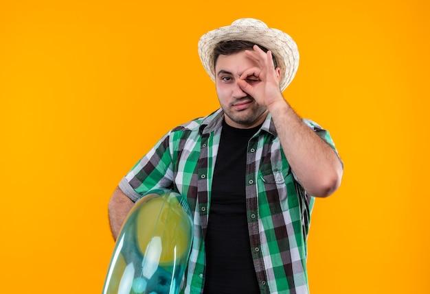 Homme jeune voyageur en chemise à carreaux et chapeau d'été tenant l'anneau gonflable souriant faisant signe ok à travers ce panneau debout sur un mur orange