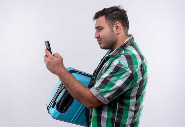Homme jeune voyageur en chemise à carreaux debout avec valise regardant l'écran de son smartphone à la confusion sur mur blanc