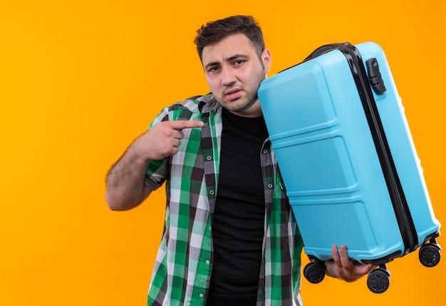 Homme jeune voyageur en chemise à carreaux holding valise pointant avec le doigt vers elle à la confusion debout sur le mur orange