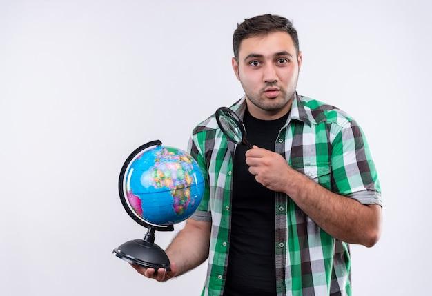Homme jeune voyageur en chemise à carreaux tenant globe et loupe à la surprise debout sur un mur blanc
