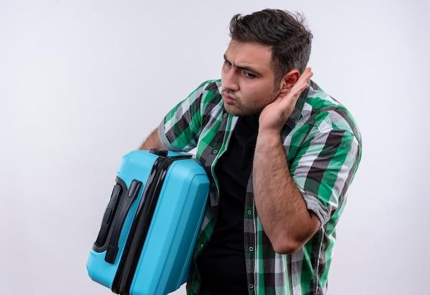 Homme jeune voyageur en chemise à carreaux tenant valise tenant la main près de l'oreille en essayant d'écouter quelqu'un conversation debout sur mur blanc
