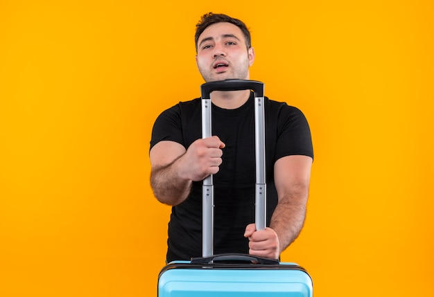 Homme jeune voyageur en t-shirt noir tenant une valise à la confiance, prêt pour des vacances debout sur un mur orange