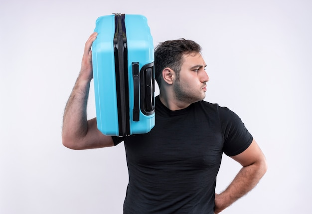 Homme jeune voyageur en t-shirt noir tenant valise à côté avec visage sérieux debout sur un mur blanc