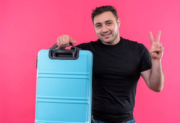 Homme jeune voyageur en t-shirt noir tenant valise heureux et positif avec sourire sur le visage montrant le signe de la victoire debout sur le mur rose