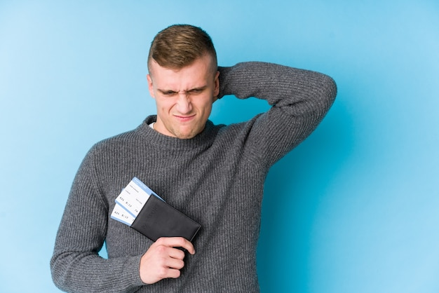 Homme jeune voyageur tenant une carte d'embarquement touchant l'arrière de la tête, en pensant et en faisant un choix.