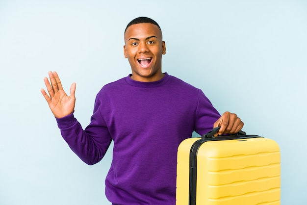Homme jeune voyageur tenant une valise isolée recevant une agréable surprise, excité et levant les mains.