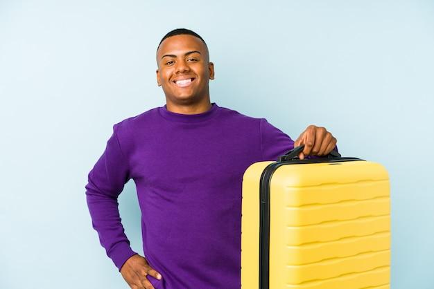 Homme jeune voyageur tenant une valise isolée en riant et en s'amusant.