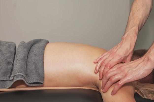 L'homme de jeunes athlètes apprécie le massage de bien-être sportif dans le cabinet médical de la salle de fitness. massothérapeute professionnel à domicile fait des exercices. concept de détente, beauté, santé, soins du corps. espace de copie