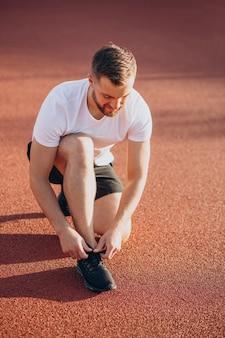 Homme jogger attachant des lacets au stade