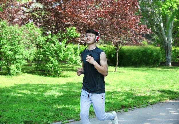 Homme jogging avec des écouteurs dans le parc