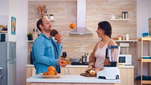 Un homme jongle avec des oranges pour sa femme dans la cuisine pendant qu'elle prépare des fruits pour un smoothie. joyeuse famille faisant ensemble du jus savoureux nutritif frais et sain pour le petit-déjeuner à partir de fruits frais whi