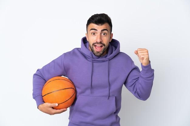 Homme jouant au basket-ball sur un mur blanc isolé célébrant une victoire en position de vainqueur