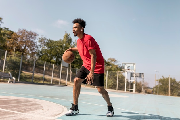 Homme jouant au basket en plein air