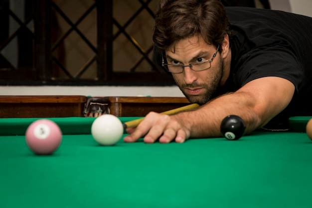 Homme jouant au billard dans une table de billard.