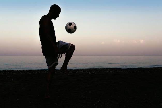 Homme jouant au football sur la plage.