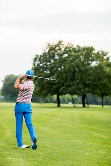 Homme jouant au golf par une journée ensoleillée sur un magnifique parcours de golf