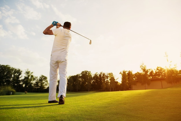 Homme jouant au golf en prenant un coup de balançoire sur une pelouse.