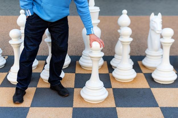 Homme jouant aux échecs gigantesques à l'extérieur