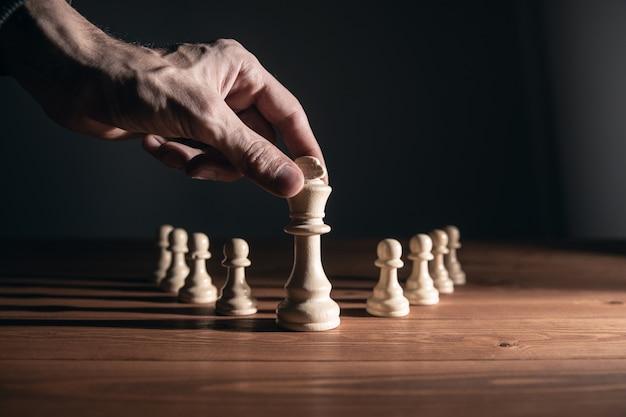 Un homme jouant aux échecs sur un mur sombre