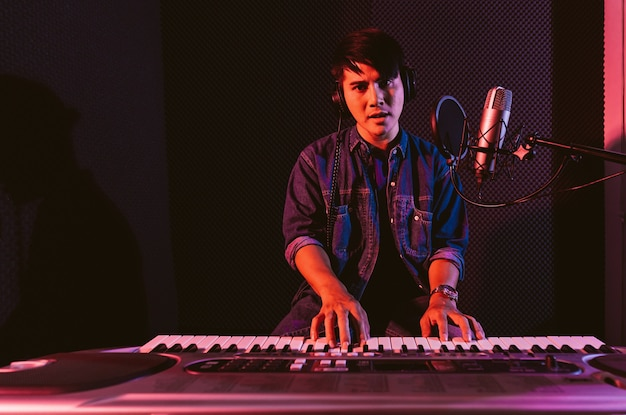 Homme jouant d'un clavier électrique tout en portant des écouteurs enregistrement de chansons