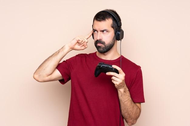 Homme jouant avec un contrôleur de jeu vidéo sur un mur isolé ayant des doutes et pensant