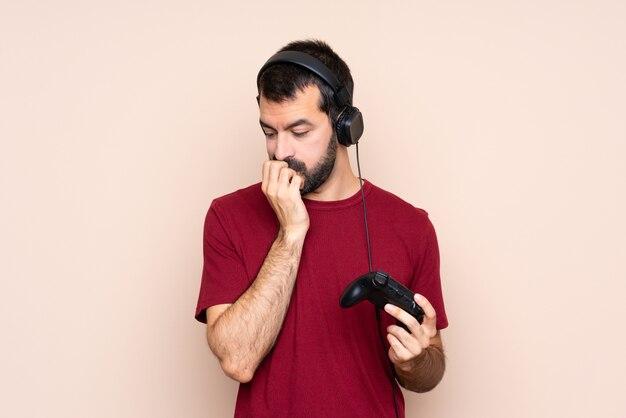 Homme jouant avec un contrôleur de jeu vidéo sur un mur isolé ayant des doutes