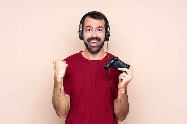 Homme jouant avec un contrôleur de jeu vidéo sur un mur isolé célébrant une victoire en position de vainqueur