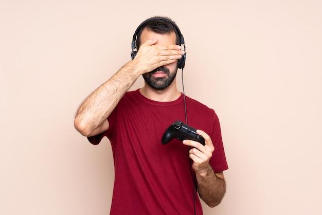 Homme jouant avec un contrôleur de jeu vidéo sur un mur isolé couvrant les yeux par les mains. je ne veux pas voir quelque chose