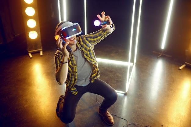 Homme jouant dans un casque de réalité virtuelle et une manette de jeu dans un cube lumineux. intérieur du club de jeu sombre, technologie vr avec vision 3d