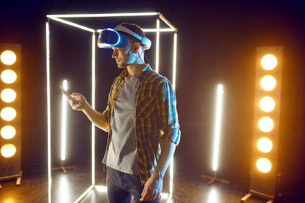 Homme jouant dans un casque de réalité virtuelle et une manette de jeu dans un cube lumineux. intérieur du club de jeu sombre, technologie vr, vision 3d